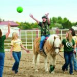 Student catching a ball during a therapeutic riding session