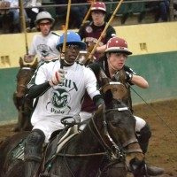 two players battle for the ball at a polo match