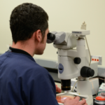 student looking into microscope